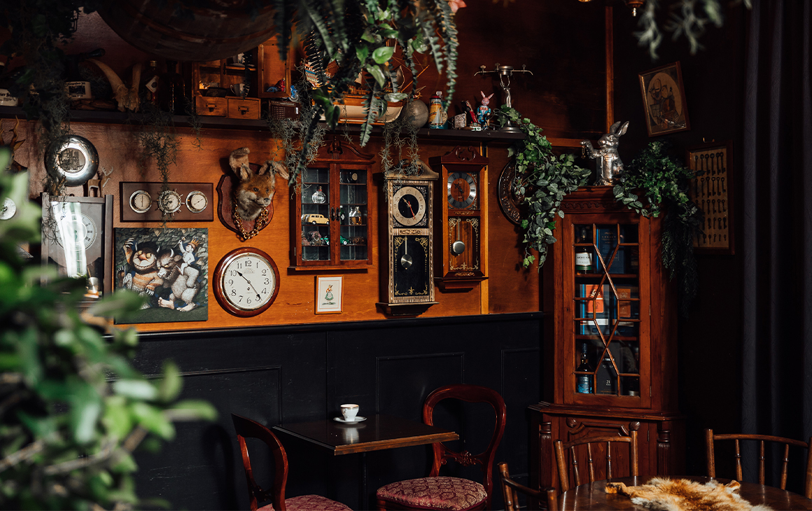 interior of a bar with clocks on the walls and vines hanging from the ceiling