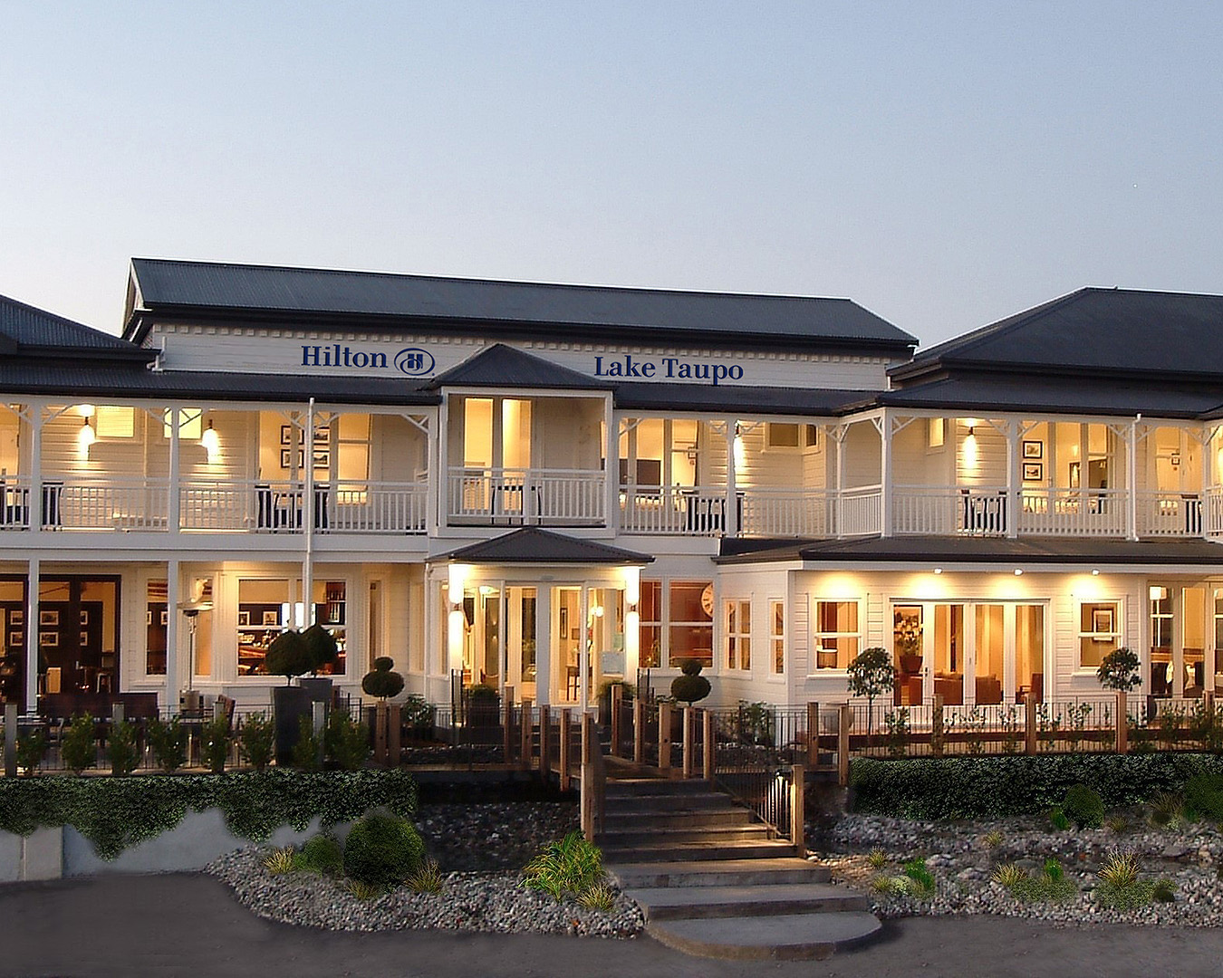 The exterior of Hilton Lake Taupo lit up by lights at dusk.