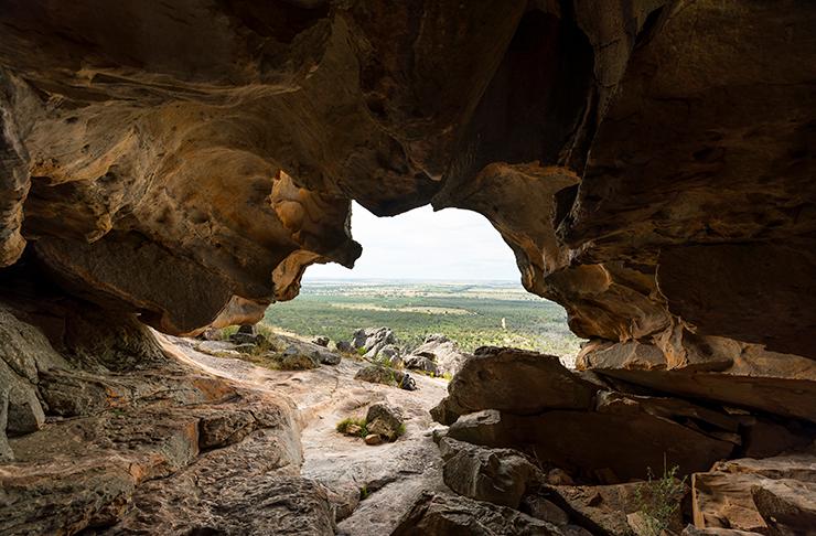 A hollow cave overlooking grass plains.