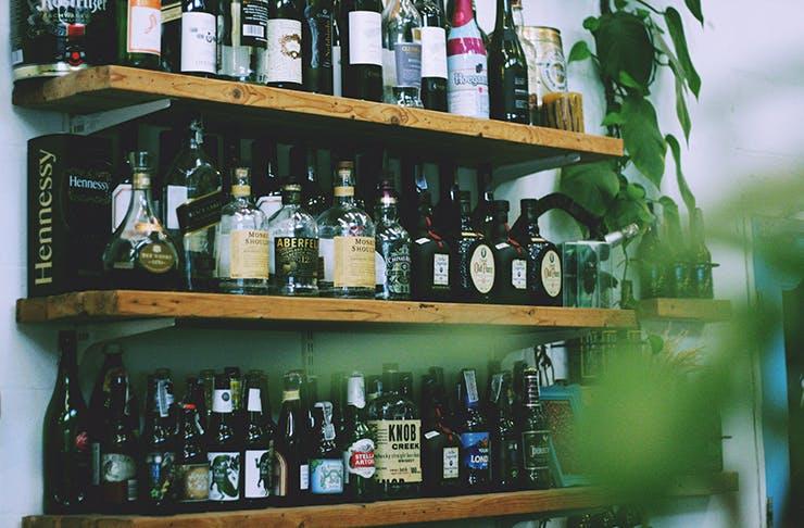A shelf full of home bar essentials, including alcohol and stirrers.