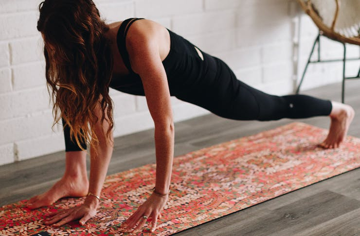 Woman in workout gear doing a forward lunge as she does pilates on a mat in her lounge room.