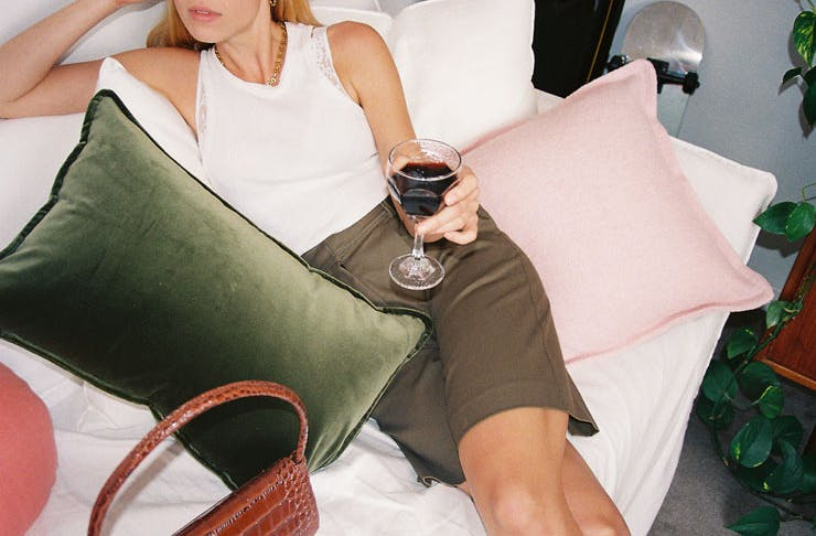 A woman reclining with some velvet cushions and a glass of wine.