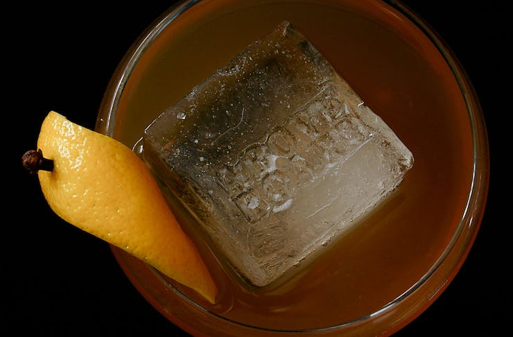 An Amaro Hot Toddy from above, a large ice cube and lemon garnish can be seen.