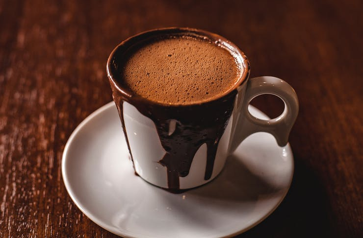 A china cup and saucer liberally overflowing with rich dark chocolate on a dark table.