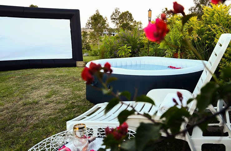 an inflatable. hot tub and movie screen in the backayrd