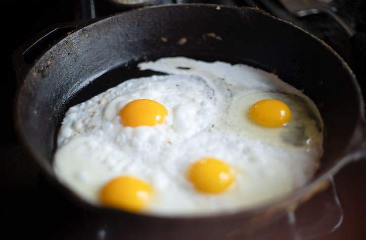 Four eggs cooking in a cast iron pan. One has just been cracked into the pan.