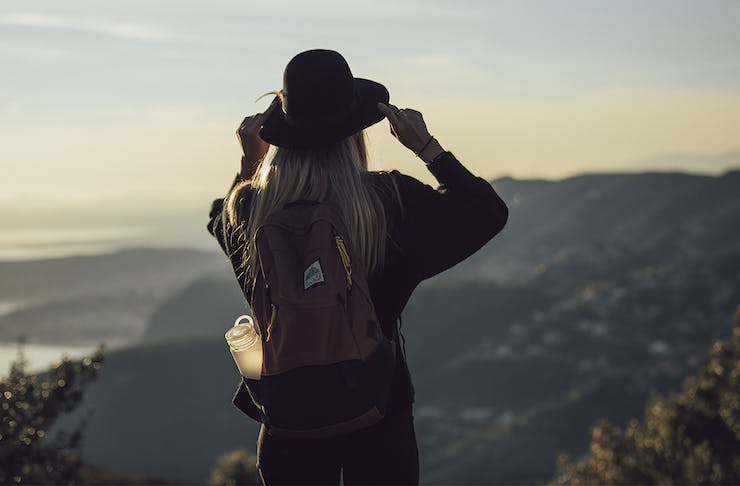 a woman on a mountain top with a backpack and a waterbottle