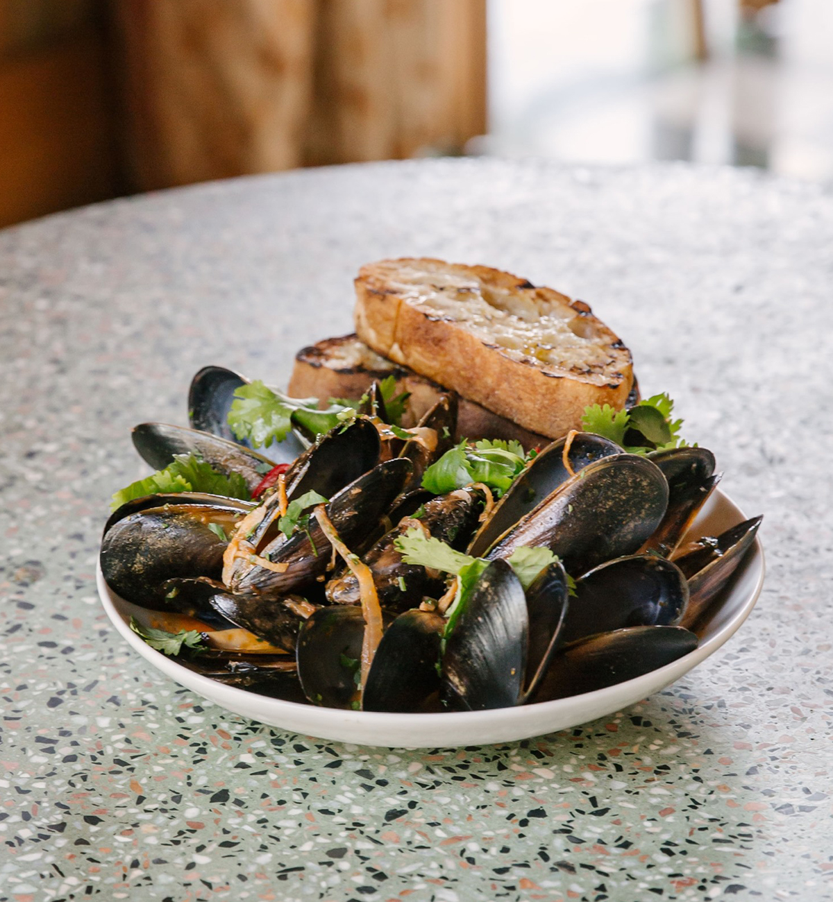 a bowl of mussels topped with crusty bread