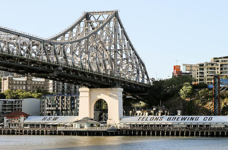 The story bridge reaching out over the river and wharves precinct