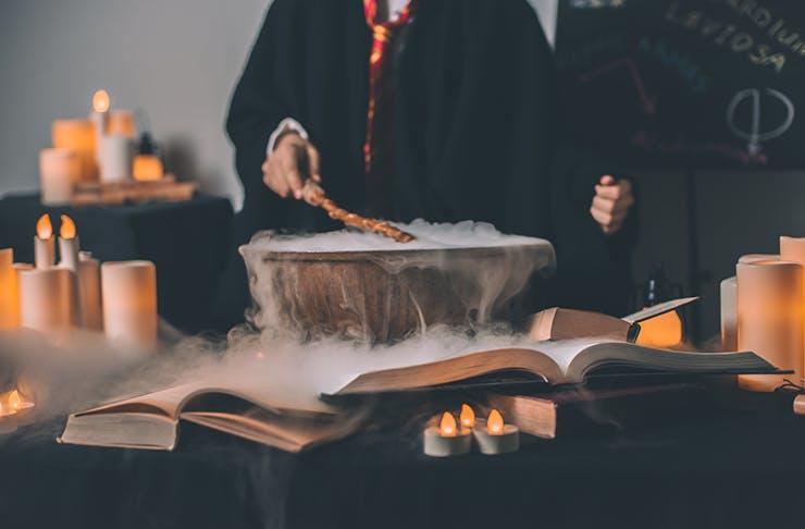 A steaming cauldron and a person waving a wand.