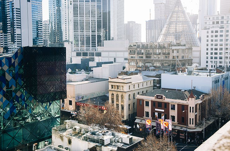 Several buildings on Melbourne's Lonsdale Street. A light mist floats above the city skyline in the morning.
