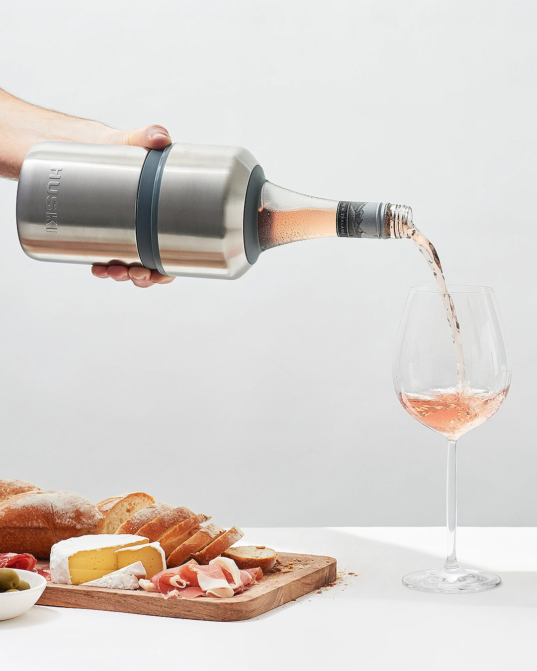 A person pours perfectly chilled rose from a stainless steel Huski wine cooler.