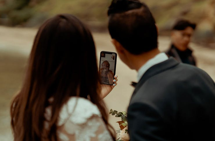 A couple getting married with a family member on Facetime.
