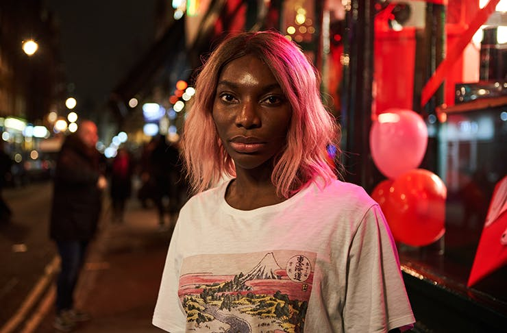 Michaela Coel in the series I May Destroy You, standing on a brightly-lit street at night.