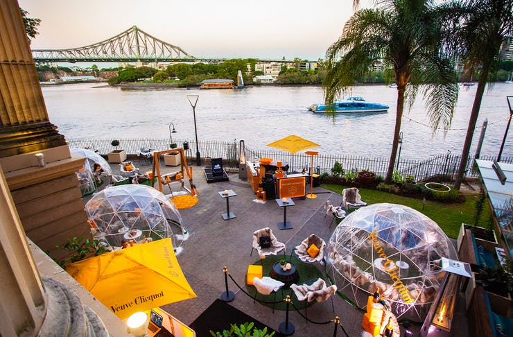 several clear plastic igloos by the river overlooking the Story Bridge