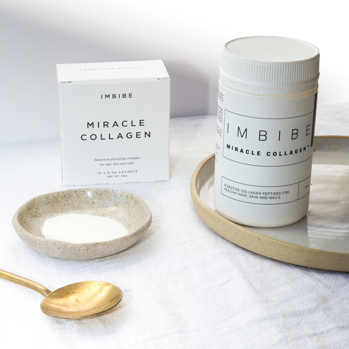 a jar of imbibe collagen next to a clay bowl