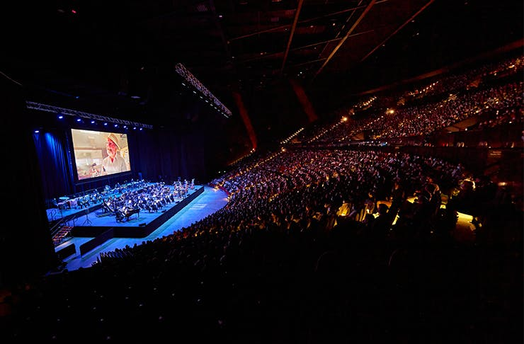 An orchestra playing in front of giant screen.