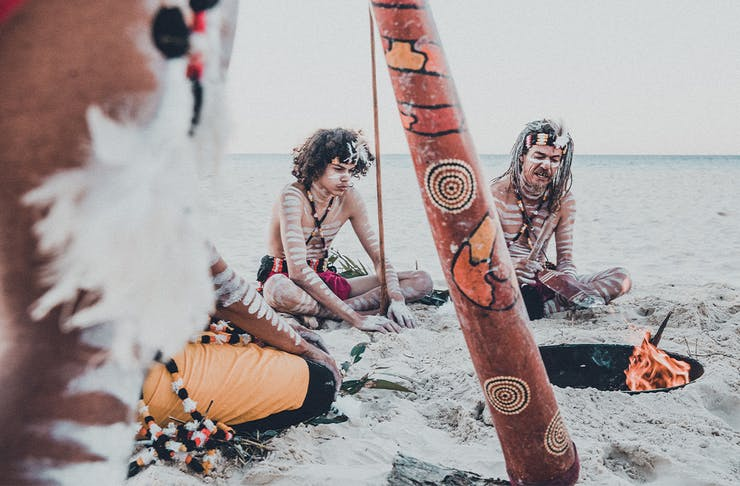 several people in indigenous paint and outfits sitting on a beach