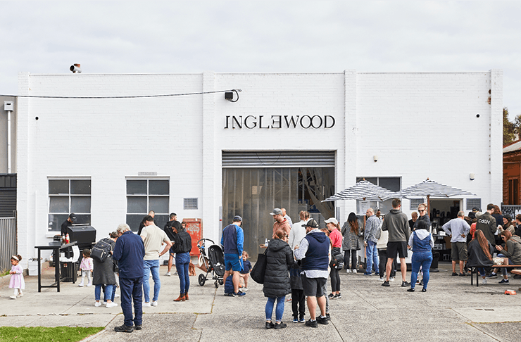 The exterior of Inglewood roastery a white brick building with people lining up out front.
