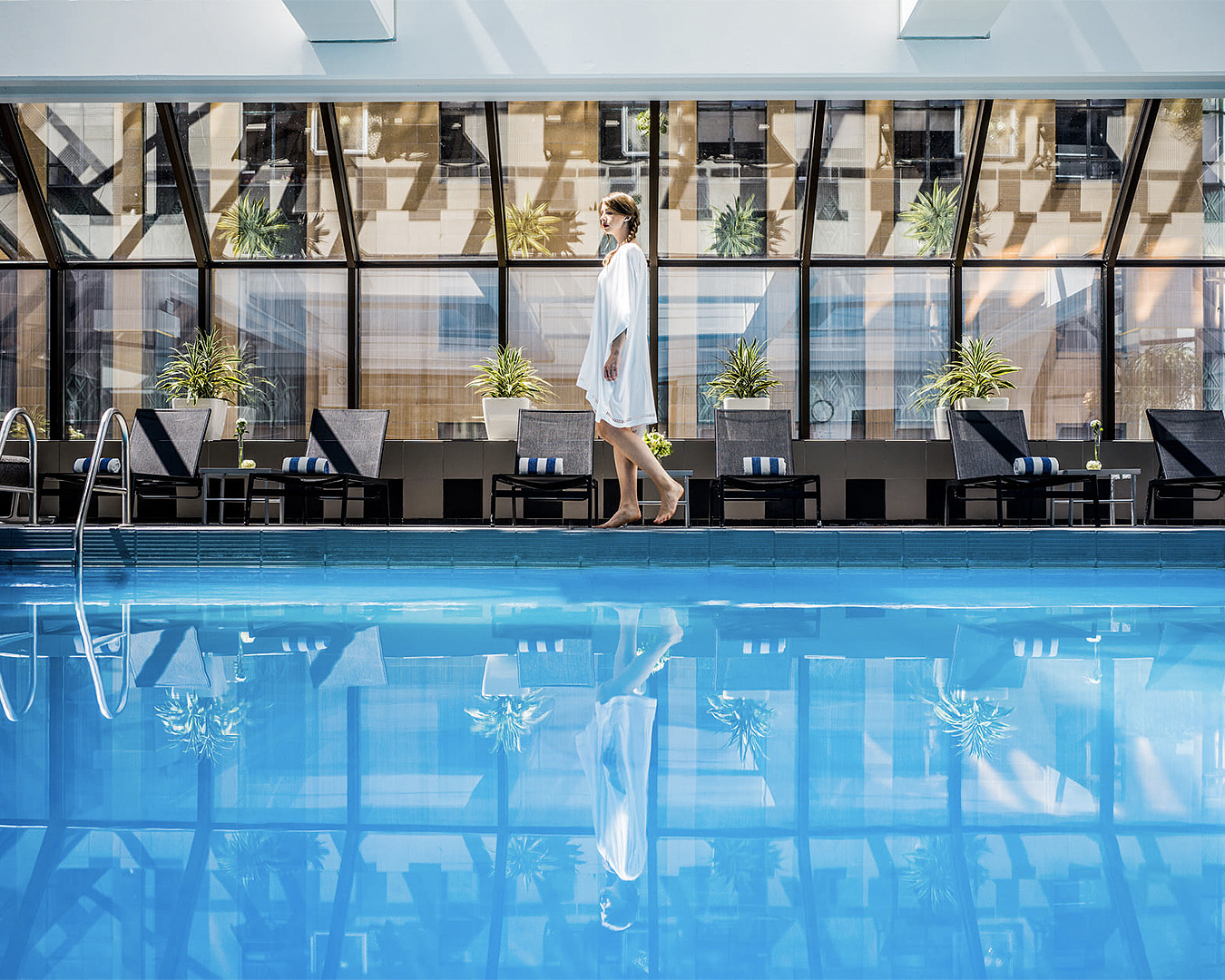 A woman walks by the large pool at the Intercontinental Hotel in Wellington, one of the best luxury hotels in New Zealand.