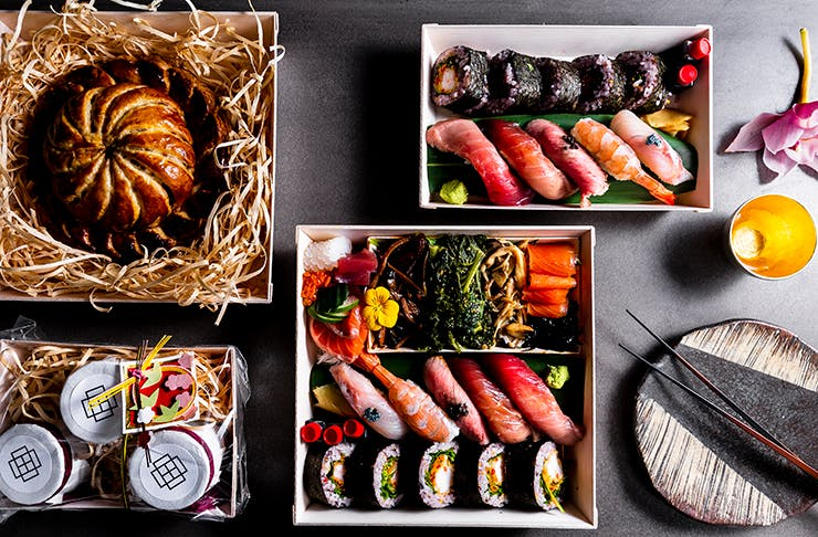 A box made of stone filled with sushi and sashimi.