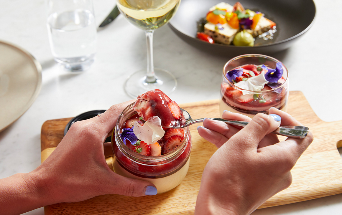 a spoon being scooped into a glass jar of a creamy, strawberry topped dessert