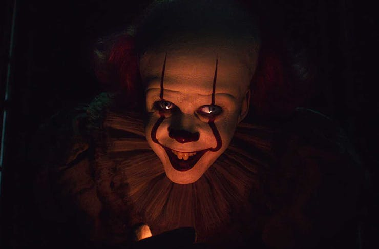A scary clown facing the camera with a menacing look on the set of It: Chapter 2.