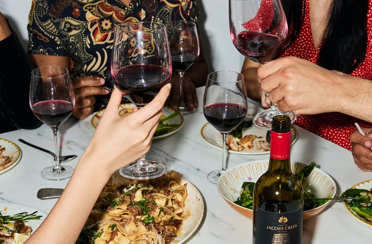 A group of people toasting with wine at a dinner.