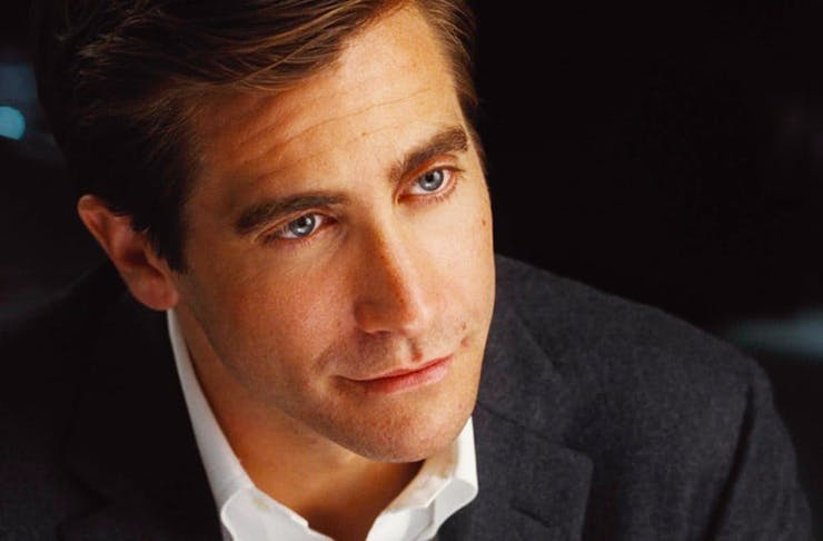 Jake Gyllenhaal in a suit, while pensively looking at the camera.