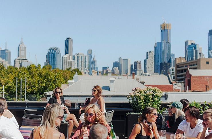 People enjoying a drink on a rooftop bar. Melbourne skyline is in the background.