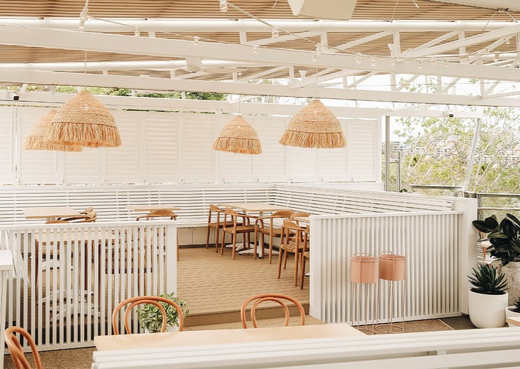 a white dining area with rattan light hangings