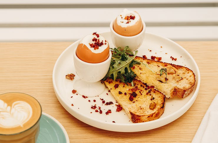 two soft boiled eggs in egg cups with toast soldiers