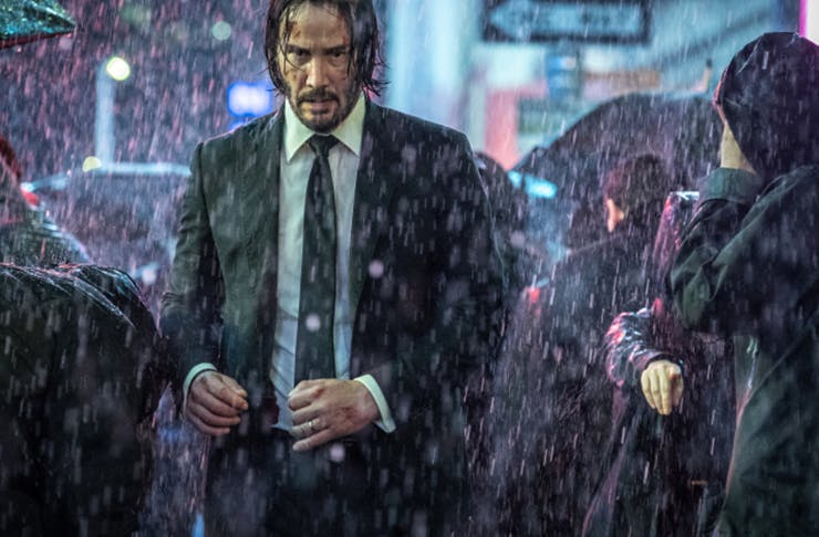 Keanu Reeves on the set of John Wick, walking through the rain in a suit