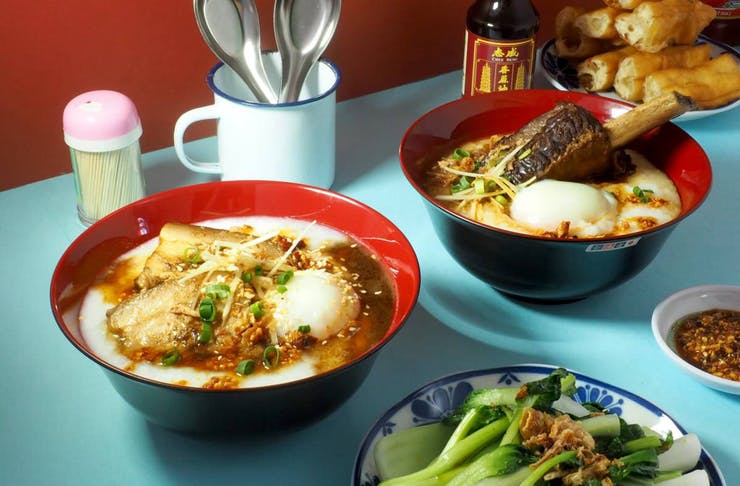 A bowl of Jok Club's congee on a table with other dishes.