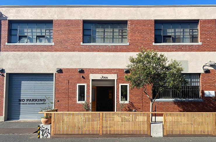 A brick building with a wooden fence out front.