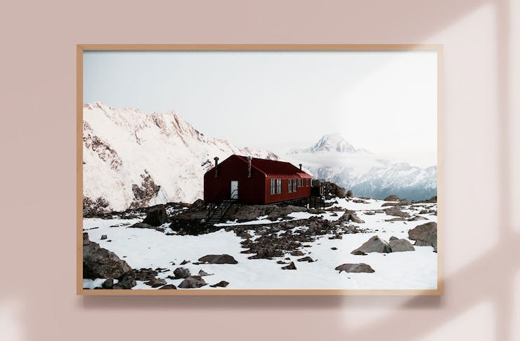 A snow topped cabin in New Zealand framed on a wall. Photo is by Jackson Loria.
