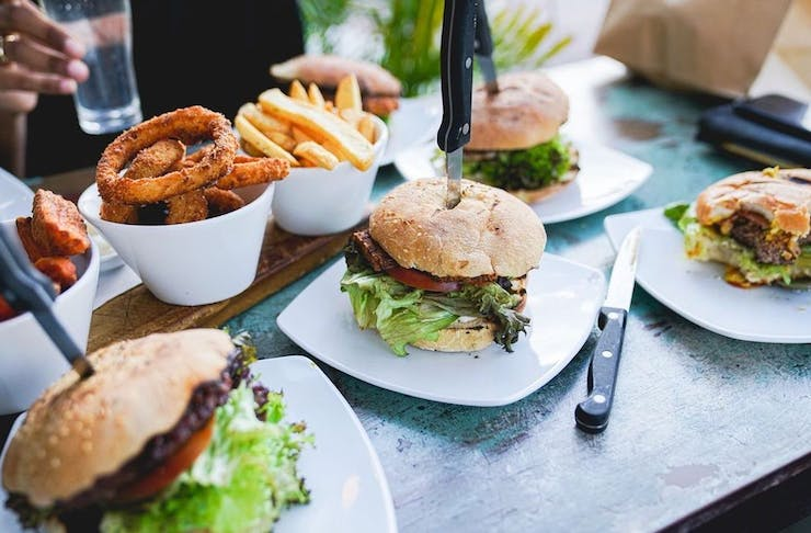 Table filled with plates of burgers and fries