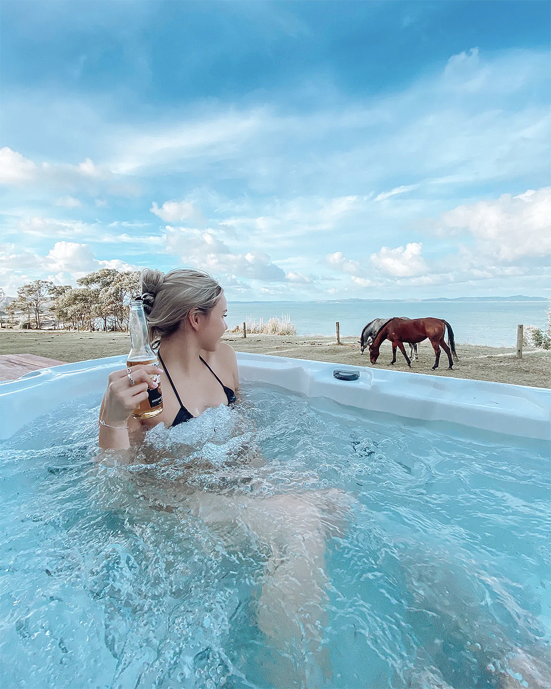 A woman looks at horses grazing from a hot tub.