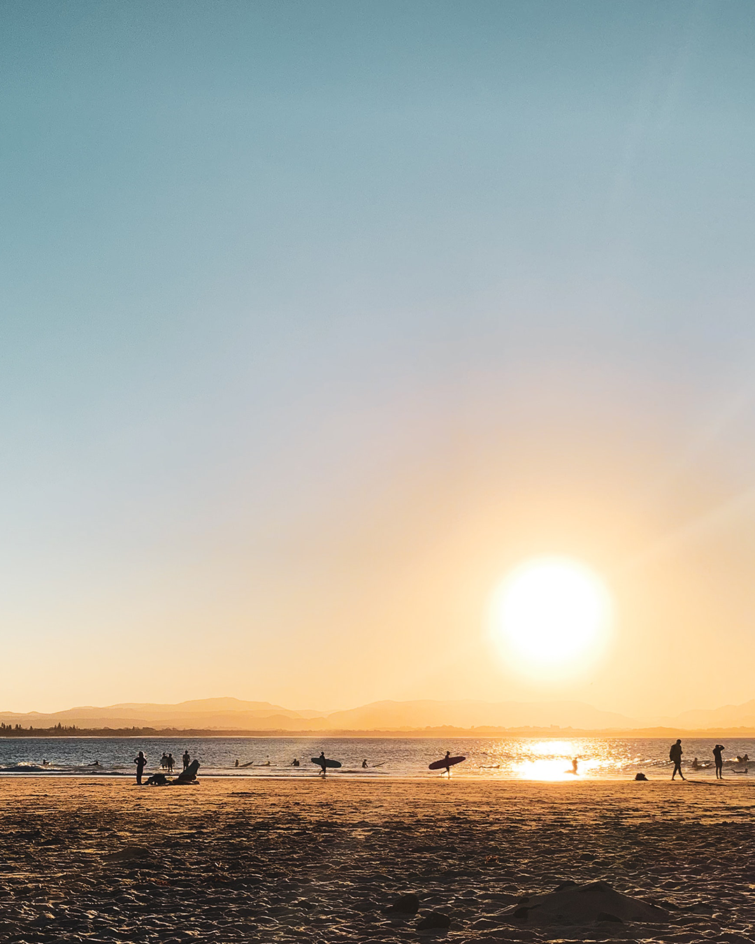 sunset at the beach with dreamy mountains in the background an surfers scattered on the beach.