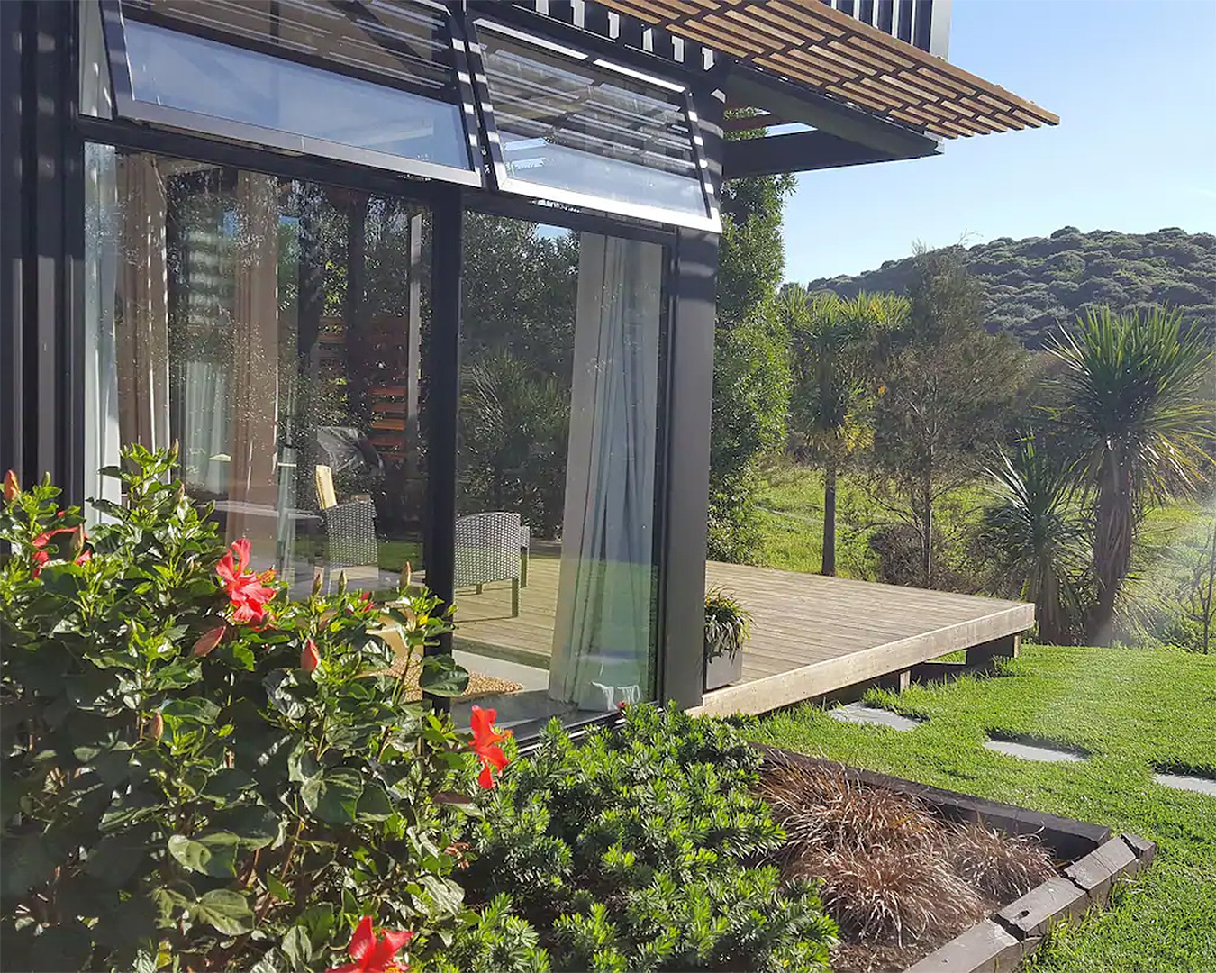 The outside of the Kauri Tree Retreat showing a building looking onto a lovely garden.