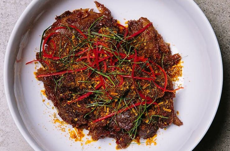 spicy looking duck curry on a white plate