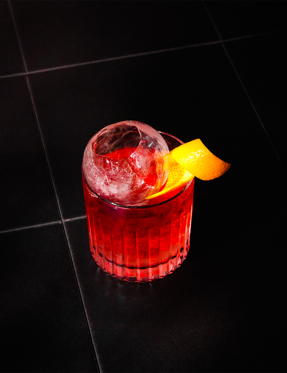 a red cocktail with an ice sphere on top