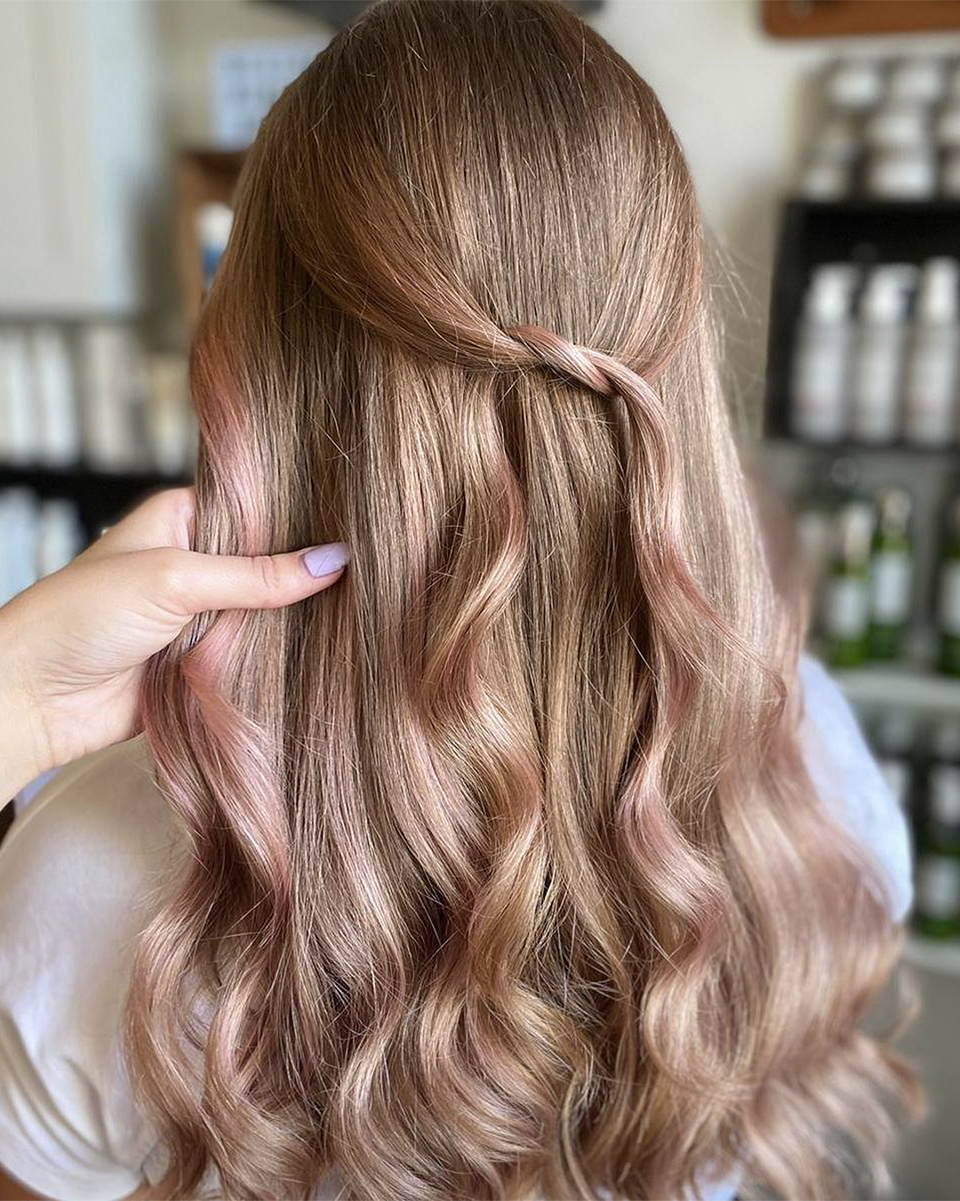 A woman with her back to the camera showing her softly pink wavy hair.