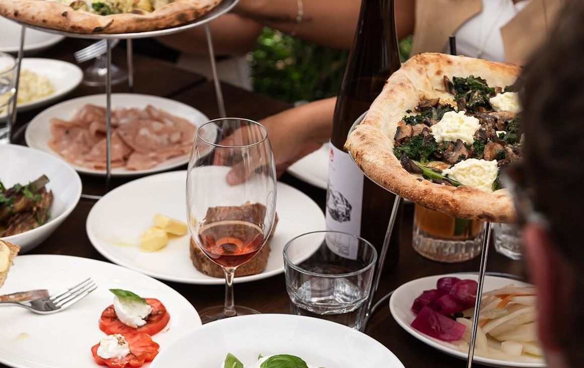 A table filled with pizza, nibbles and wine at King Somm