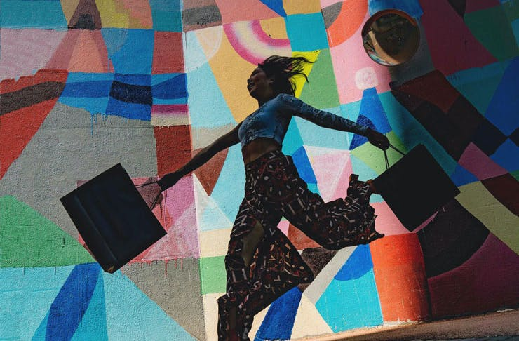 A woman with shopping bags in front of some colourful street art.