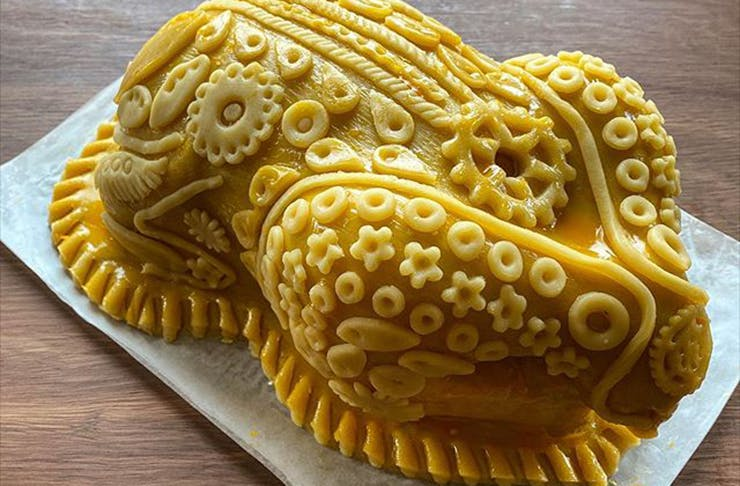 A chicken encrusted and decorated in pastry.