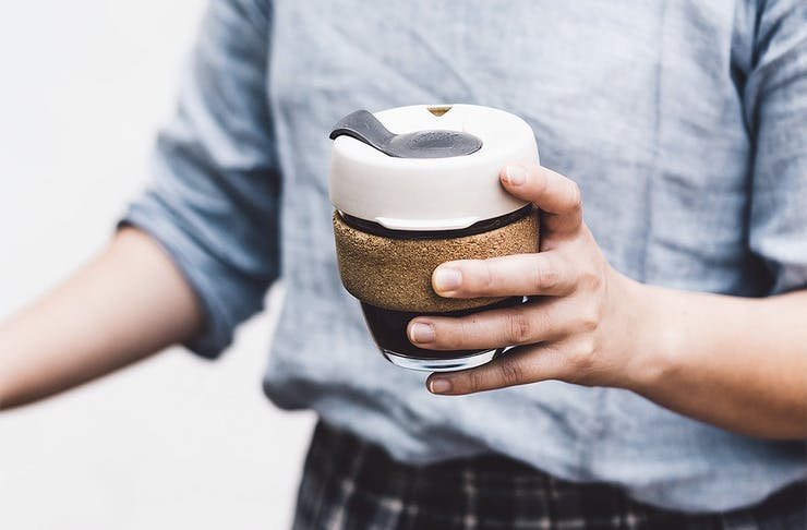 A person holds a keep cup in their hands.
