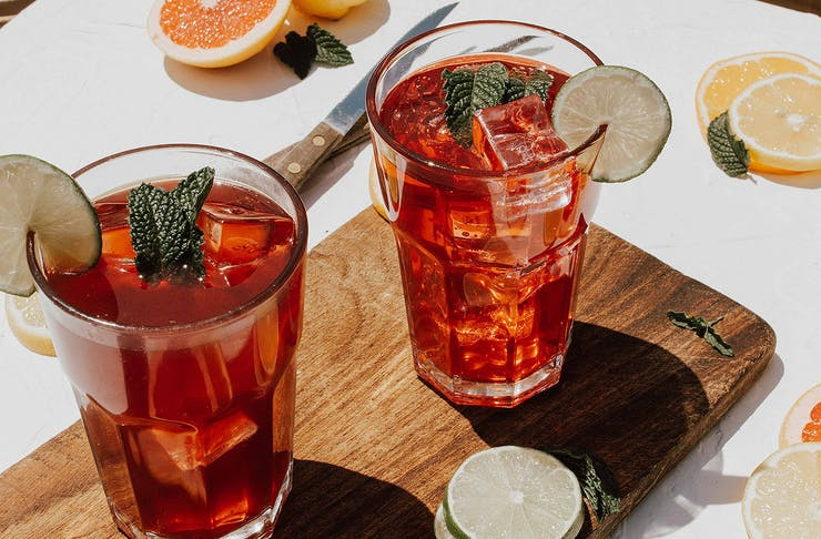 A couple of glasses of kombucha sit on a wooden board surrounded by slices of lemon and orange.