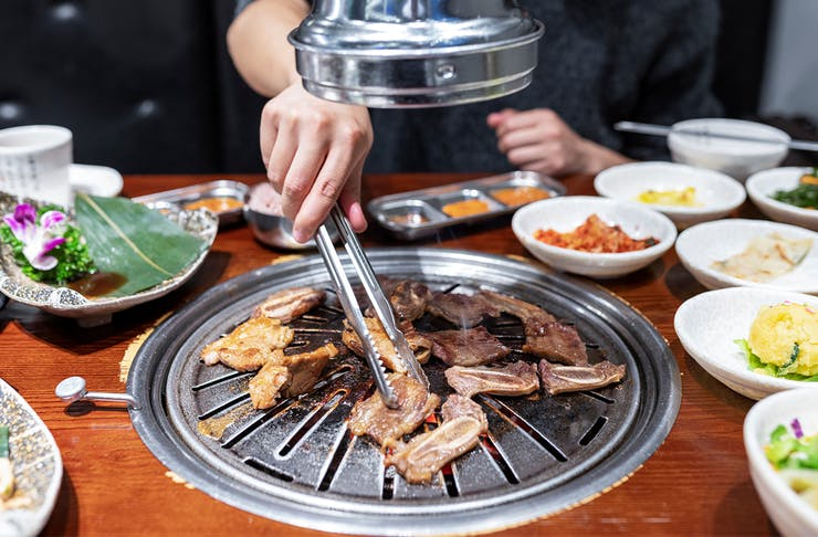 a person using tongs to turn meat cooking on a sunken bbq in a table