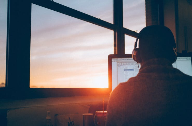 Man checking emails behind sunset window